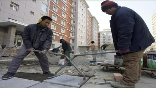 Chinese workers work at the compound of a residential apartment for foreigners in Beijing Tuesday, Dec. 27, 2005. China said its economy is much bigger and less export-dependent than previously reported, issuing new data that analysts say may ease fears its roaring growth is unsustainable, and encourage even more foreign investment. (AP Photo/Ng Han Guan)